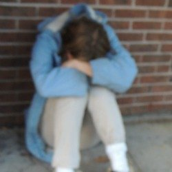 woman drug addict sitting with head between between knees
